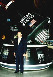 Jules Poirier next to a Gemini space capsule