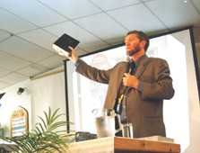 Ken Ham holding up the Bible during a lecture
