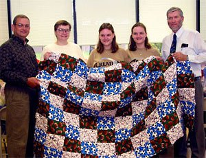 The Garcia family presents Ken Ham with their handmade quilts
