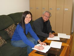 A beaming Michiko Mizumura of CRJ signs the historic agreement in Japan along with Dr. David Crandall of our staff.