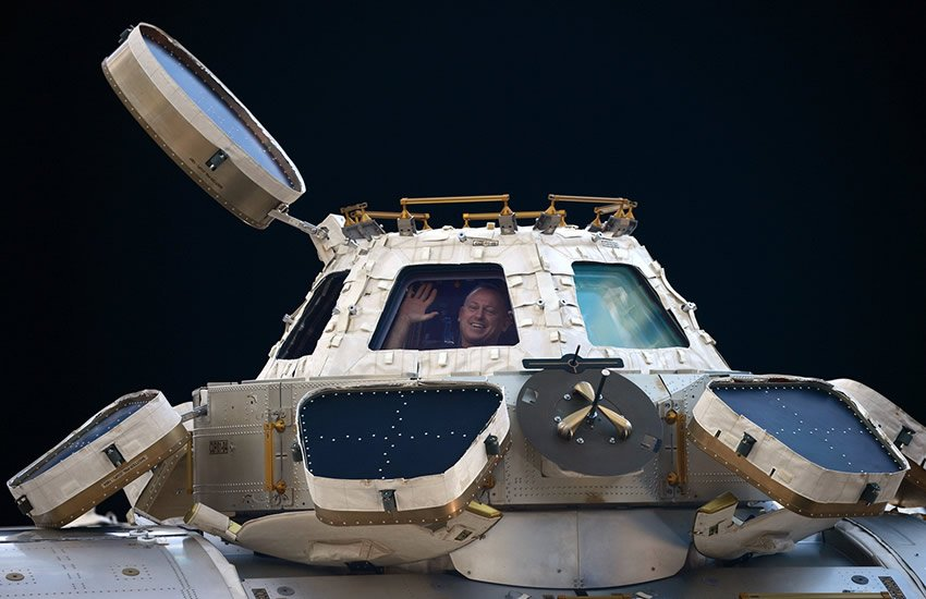 Waving from inside the International Space Station's observation cupola.