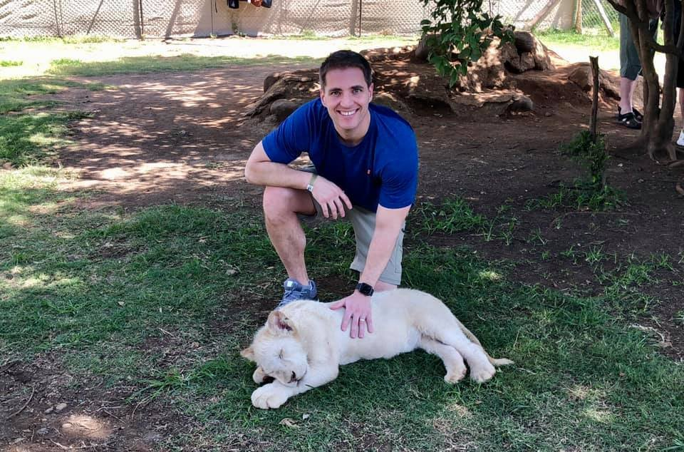Bryan Osborne hangs out with a lion cub