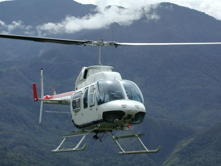 Helicopter hovering with mountain backdrop