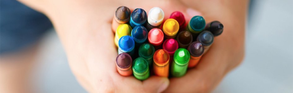 Kid's Hand Holding Crayons