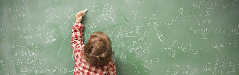 Little Boy Writing on Chalkboard