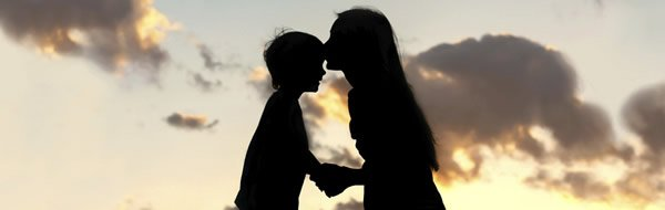 Mother kissing son's forehead